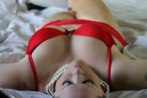 mujer estirada en la cama con lencería roja