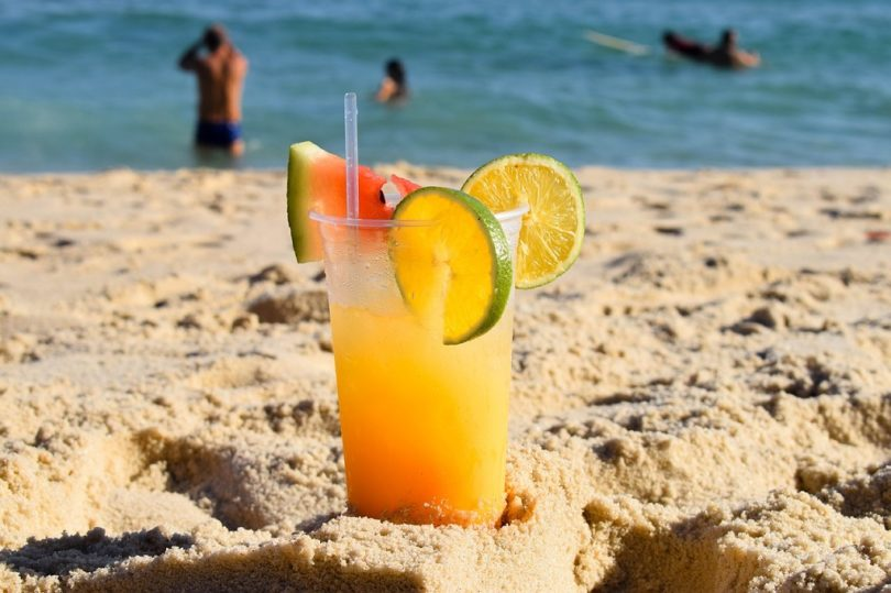 exotic cocktail in sand with sea behind it