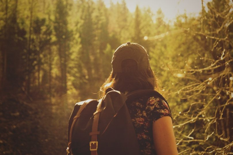 lady with rucksack walking through forest