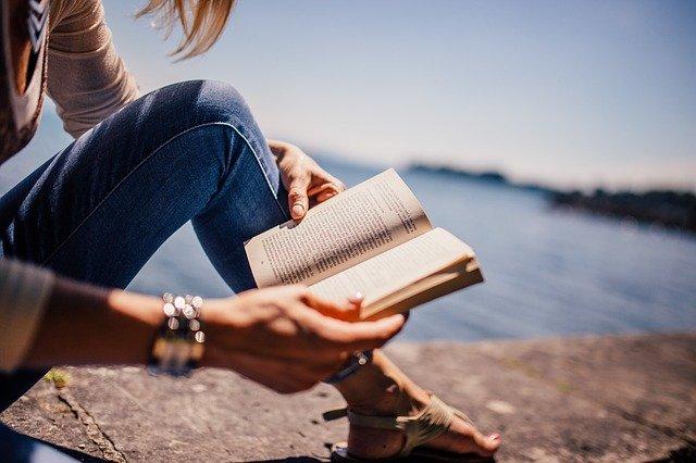woman reading book near water