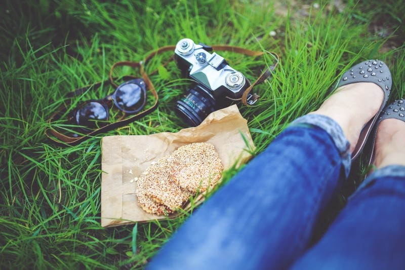legs with blue jeans in grass, with camera, sandwiches and sunglasses
