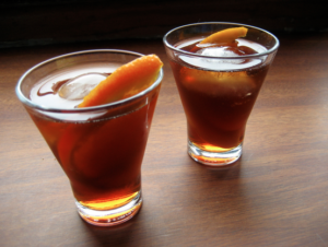 two glasses of vermut with ice and slice of orange on wooden table