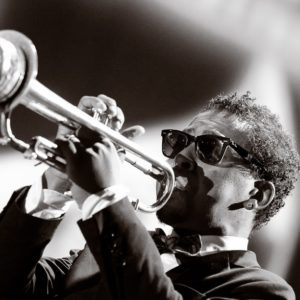 man playing trumpet with glasses