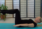 blonde lady doing pilates exercise on mat