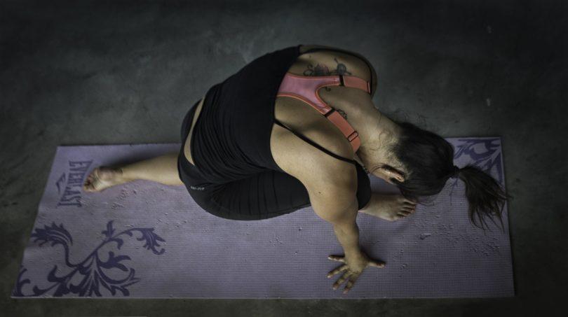 lady in dark environment in yoga pose on purple yoga mat