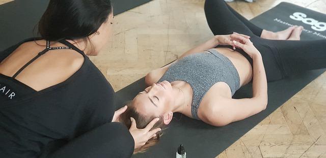 yoga teacher and student on floor