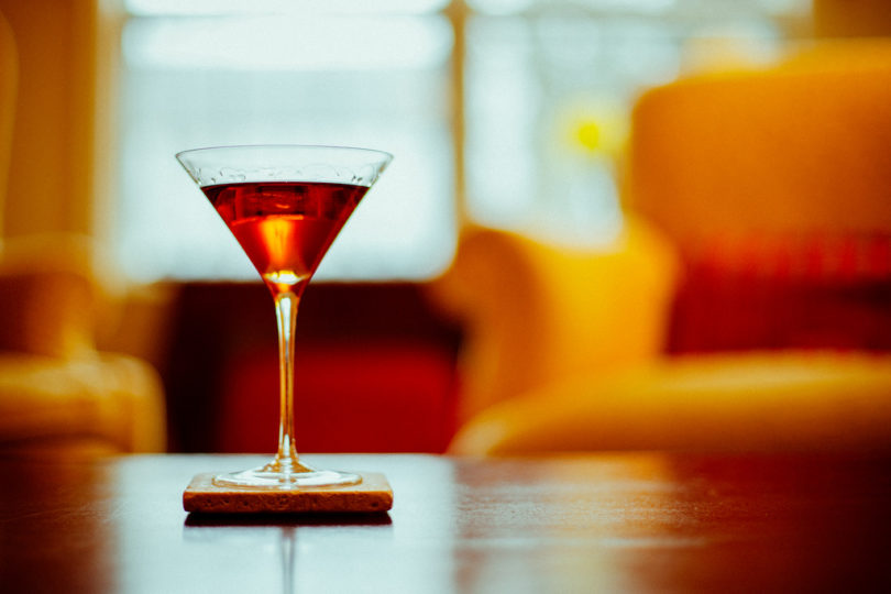 vermouth in glass on bar with orange chair in background