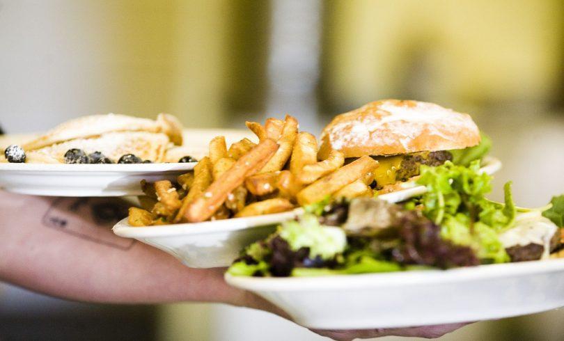 three plates, salad, hamburger and fries and pancakes