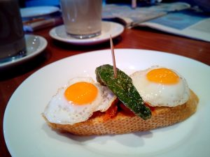 Pincho of two fried eggs and a spicy pepper