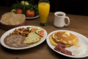 pancakes, eggs, bacon, coffee and orange juice