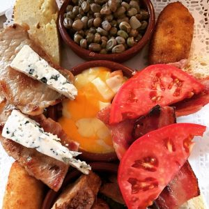 Mix of food in a plate with some tomatoes, cheese, meat and bread
