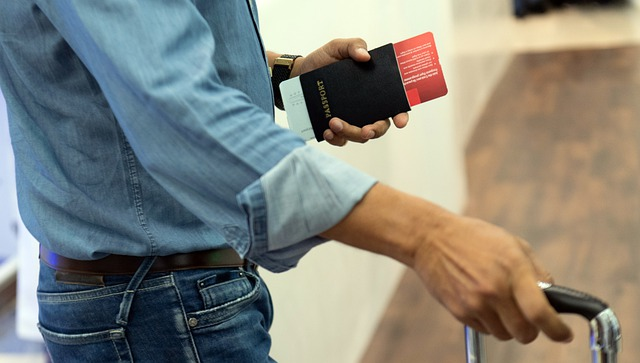 man with boarding pass and passport in hand