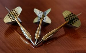 three darts on a wooden table