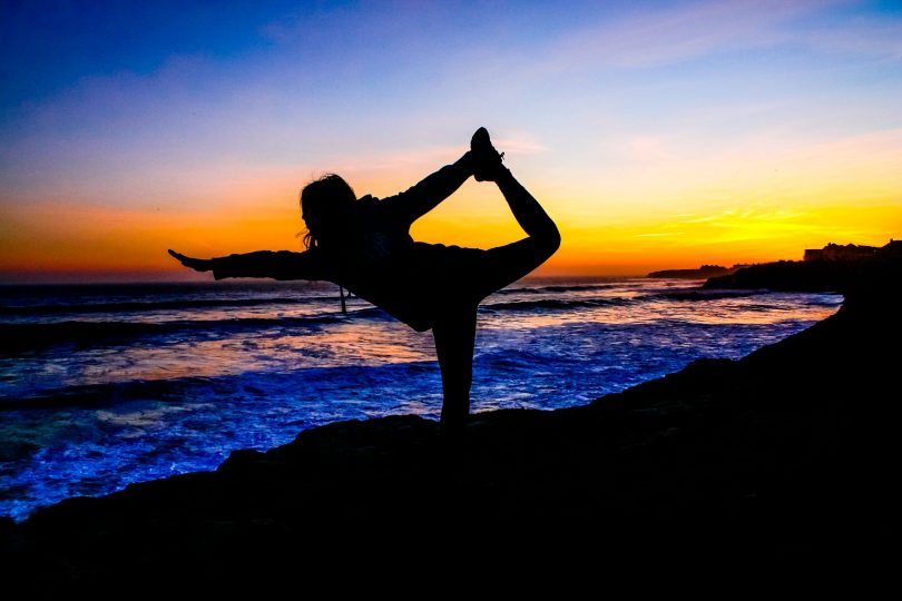 lady doing yoga exercise on beach when sun has just set