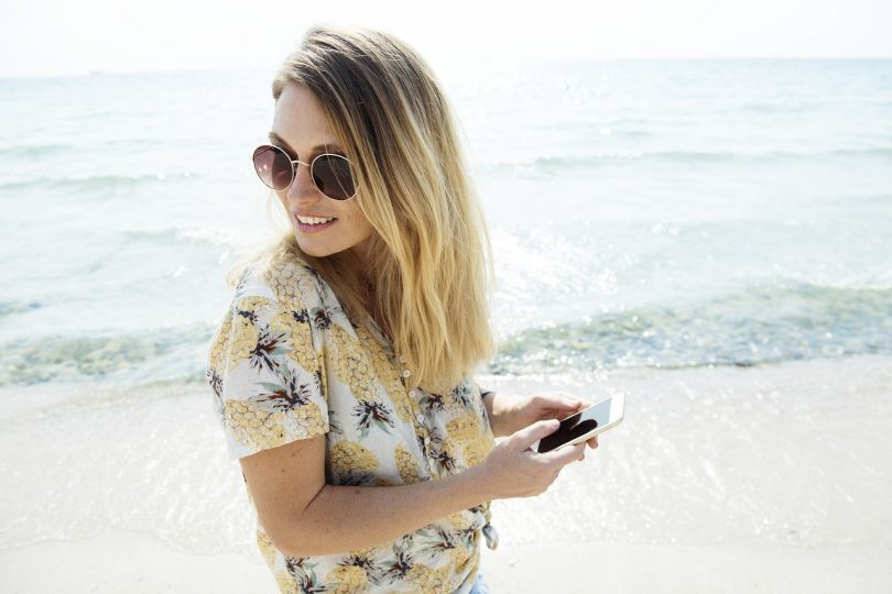lady in floral blouse and sunglasses with phone in her hands