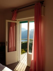 balcony with open door and pink curtains