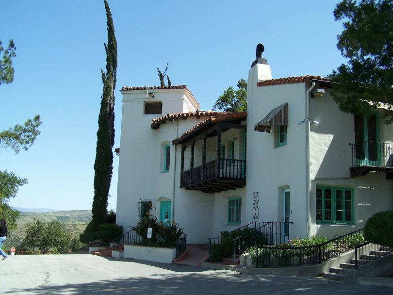 large white spanish house with trees