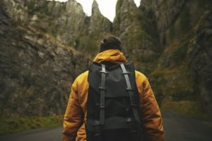 hiker with yellow jacket and backpack in mountains