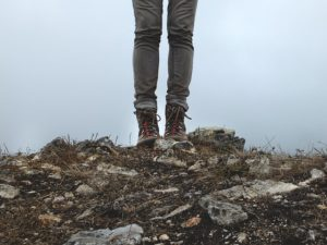 legs of hiker on top of mountain with fog