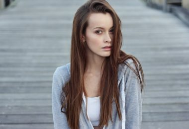 lady with brown hair in white top and grey vest