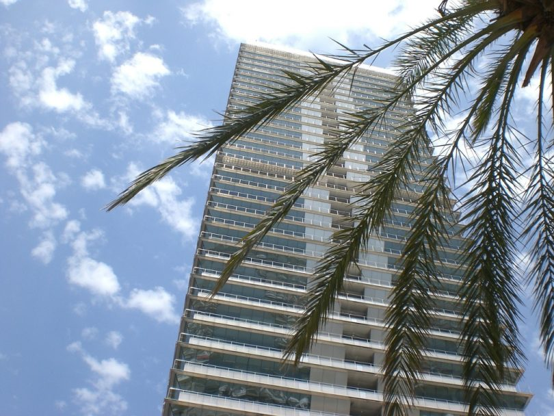 exterior apartment building with blue sky and palm tree