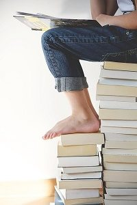 person sitting on pile of books