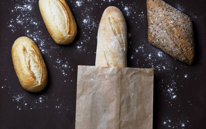 black table with baguette and whole grain bread
