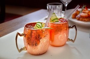 two cocktails in copper cups with piece of cucumber