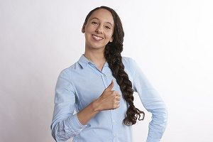 female in blue blouse with thumbs up and smile
