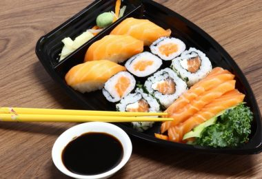 plate of salmon sushi with chop sticks and soya sauce