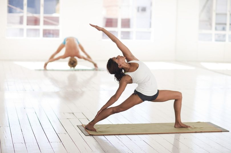 two people doing yoga in light room
