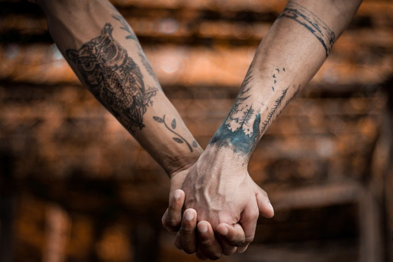 Two persons wearing tattoos on the arms and holding hands.