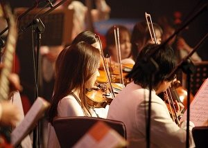 orchestra with lady playing the violin