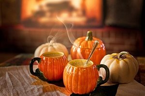 coffee cups in the shape of pumpkins before a fire place