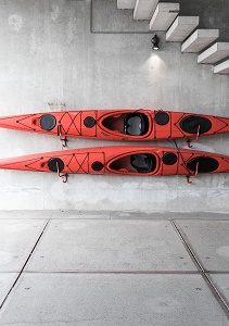 two kayaks on the wall under concrete stairs