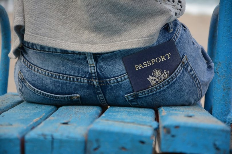 passport in back pocket of person sitting on blue bench