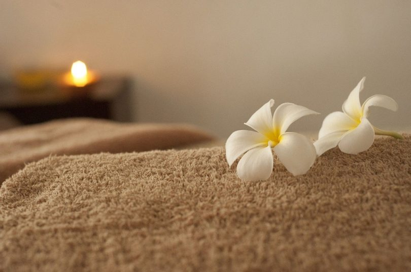 beige towel with white flower and candle