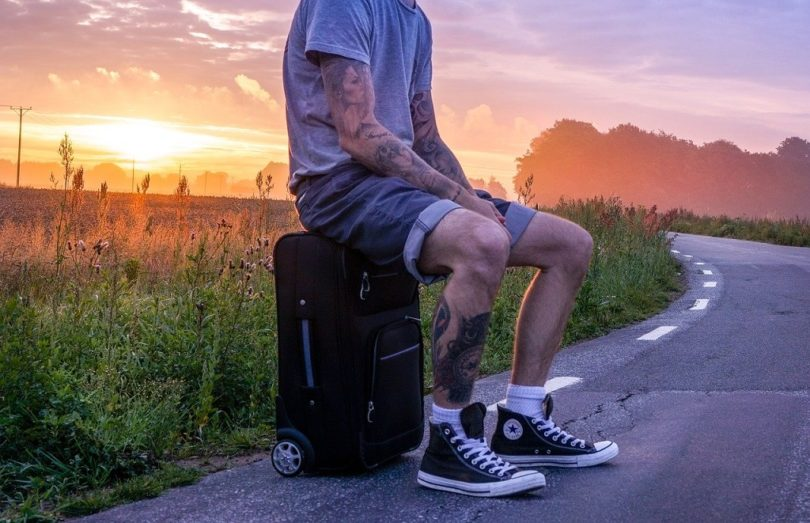 man with tattoo sitting on suitcase