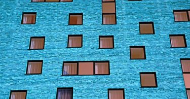 blue apartment building with uneven windows