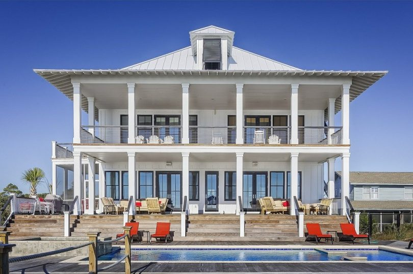 white, two story house with pool in front