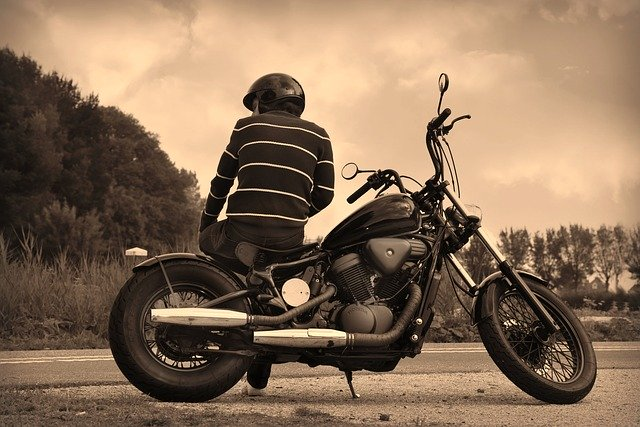 man sitting sideways on motorcycle