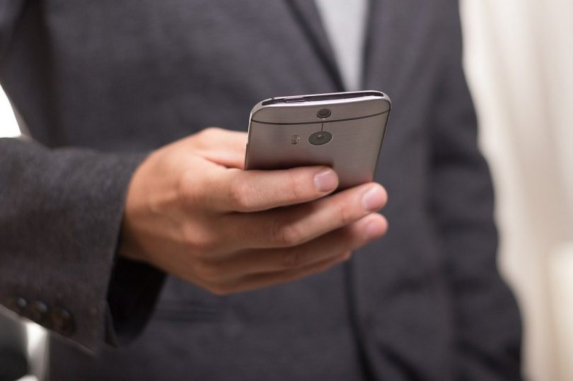 man in suit looking at phone