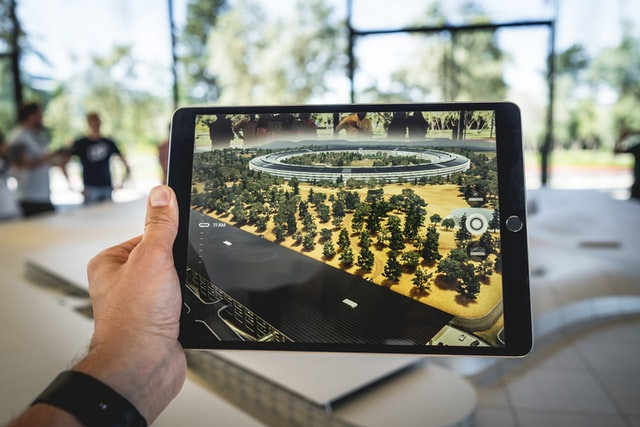 person holding black iPad photo, real estate trends