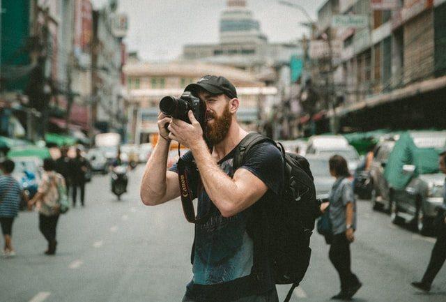 man taking photo in city