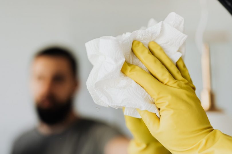 yellow cleaning glove wiping mirror