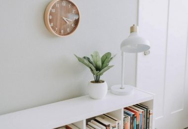 wall with clock, cabinet, lamp and plant