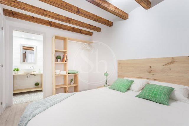 light bedroom with wooden beams