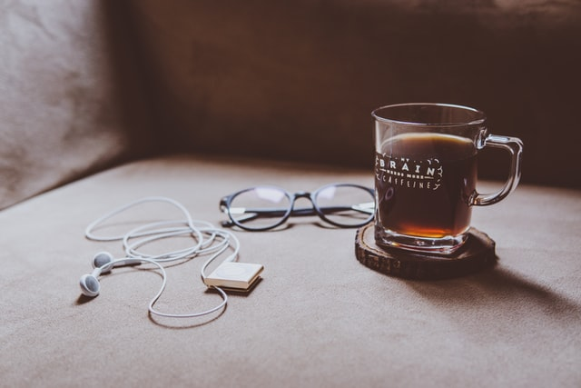 coffee, glasses and earphones on couch