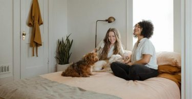 two ladies share the bed with a dog