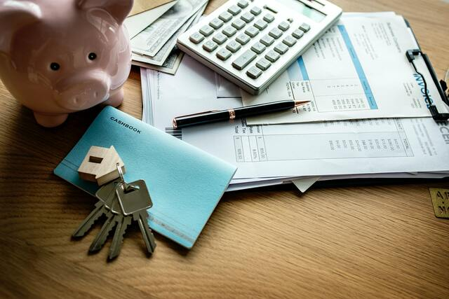 desk with papers, piggy bank and keys - guarantee rental income